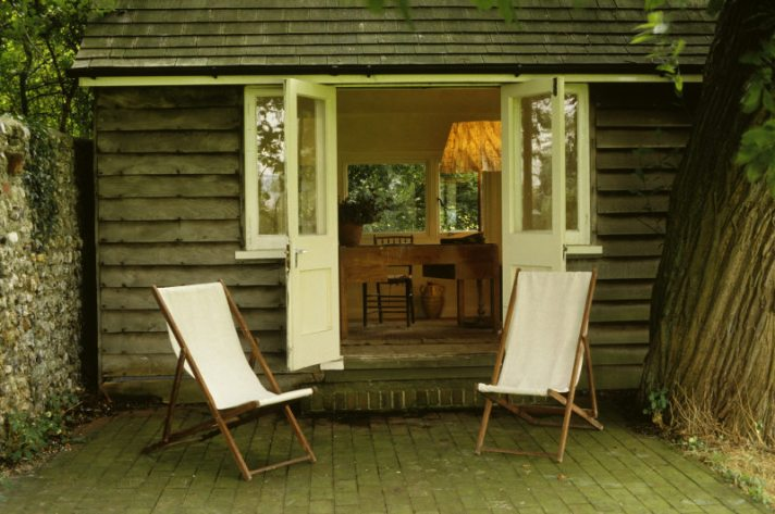 The Lodge Writing Shed in the garden at Monk's House, the former home of Virginia and Leonard Woolf. Deck chairs are placed in front of the wooden shed and a desk and lamp can be seen inside.
